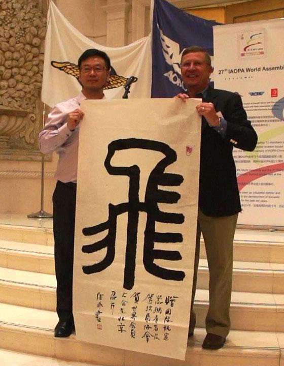 """中国AOPA副秘书长唐永先生(左)即兴书写了一个篆体""""飞""""字,赠送给国际AOPA秘书长Craig Spence(右)"""